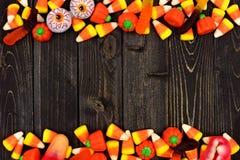 万圣夜糖果在黑暗的木头的双边界 免版税库存照片