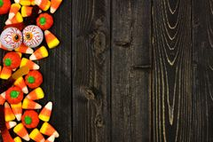 万圣夜糖果在黑暗的木头的边边界 免版税库存照片