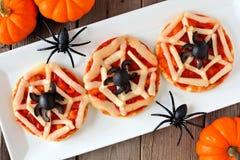 万圣夜蜘蛛网微型薄饼,在白色板材的桌场面 免版税库存图片