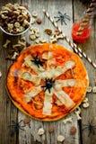 万圣夜蜘蛛薄饼用西红柿酱和乳酪在木 免版税库存照片