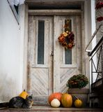 万圣夜装饰了前门用各种各样的大小和形状南瓜 在万圣夜装饰的前沿的猫 免版税图库摄影