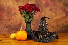 万圣夜静物画用南瓜、巫婆帽子和秋天开花 免版税库存图片