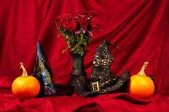 万圣夜静物画用南瓜、巫婆帽子和花 图库摄影