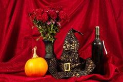 万圣夜静物画用南瓜,酒,与帽子和花 免版税库存图片
