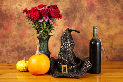 万圣夜静物画用南瓜,酒,与帽子和花 库存照片