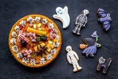 万圣夜面包店和甜点 南瓜饼,胶粘的蜘蛛,在黑背景顶视图的姜饼曲奇饼 图库摄影
