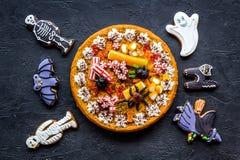 万圣夜面包店和甜点 南瓜饼,胶粘的蜘蛛,在黑背景顶视图的姜饼曲奇饼 库存图片