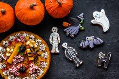 万圣夜面包店和甜点 南瓜饼,胶粘的蜘蛛,在黑背景顶视图的姜饼曲奇饼 库存照片
