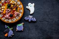 万圣夜面包店和甜点 南瓜饼,胶粘的蜘蛛,在黑背景顶视图copyspace的姜饼曲奇饼 库存照片