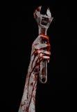 万圣夜题材:拿着在黑背景的血淋淋的手一把大板钳 免版税库存图片