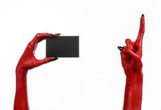 万圣夜题材:有拿着在白色背景的黑钉子的红魔手一张空白的黑卡片 免版税库存图片