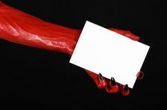 万圣夜题材:有拿着在黑背景的黑钉子的红魔手一张空白的白色卡片 免版税库存图片