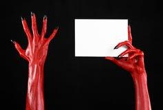 万圣夜题材:有拿着在黑背景的黑钉子的红魔手一张空白的白色卡片 免版税库存照片