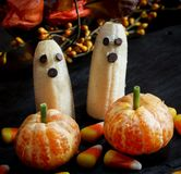 万圣夜食物香蕉鬼魂和柑桔南瓜在黑暗的鬼的背景 库存图片