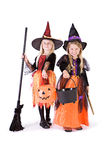 万圣夜:两个逗人喜爱的巫婆准备好糖果 免版税库存照片