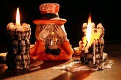 万圣夜:在以在燕尾服和帽子穿戴的骨骼的形式一个烛台蜡烛烧 库存图片