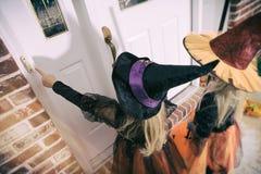 万圣夜:女孩按门铃对把戏或款待 库存照片