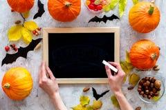 万圣节准备 笔记在南瓜中和棒的黑书桌在灰色背景顶视图大模型 图库摄影