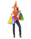 万圣节帽子的微笑的妇女与购物袋 库存图片
