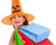 万圣节帽子的愉快的妇女与购物袋 图库摄影