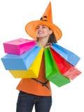 万圣节帽子的愉快的妇女与购物袋 库存照片