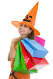 万圣节帽子的愉快的妇女与购物袋 免版税图库摄影