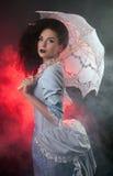 万圣节有鞋带遮阳伞的吸血鬼妇女 库存图片