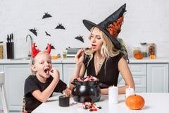 万圣节服装的吃款待从黑罐的母亲和小女儿 免版税库存图片