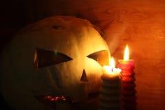 万圣节 与灼烧的眼睛和一个蜡烛的南瓜 库存照片