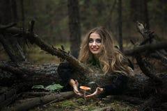 万圣节 伞形毒蕈 一件黑礼服的美丽的女孩在森林里 图库摄影