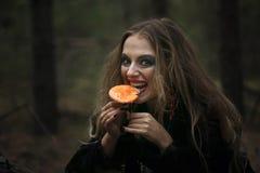 万圣节 伞形毒蕈 一件黑礼服的美丽的女孩在森林里 免版税库存照片