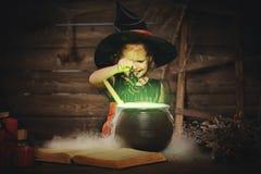 万圣节 儿童准备在大锅的女孩巫婆魔药 免版税图库摄影