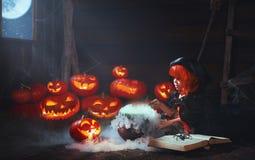 万圣节 儿童准备在大锅的女孩巫婆魔药 免版税库存照片