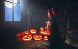 万圣节 儿童小巫婆用由窗口waitin的南瓜 库存图片