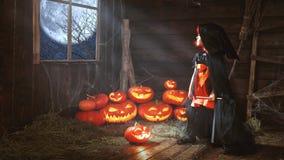 万圣节 儿童小巫婆用由窗口waitin的南瓜 图库摄影