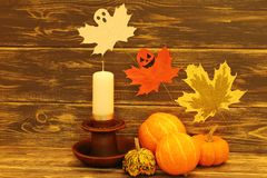 万圣节 在一个陶瓷烛台有一个白色蜡蜡烛的和飞行的恶作剧鬼魂附近的装饰多彩多姿的南瓜在Th 免版税库存照片