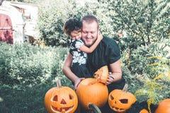 万圣节 女儿父亲拥抱 当他准备起重器o灯笼,人切开从南瓜的一个盒盖 党的装饰 被定调子的照片 库存照片