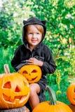万圣节 孩子在与起重器o灯笼,把戏或款待的黑色在手中穿戴了 在木头的小女孩南瓜,户外 库存图片