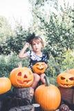 万圣节 孩子在与起重器o灯笼,把戏或款待的黑色在手中穿戴了 在木头的小女孩南瓜,户外 被定调子的p 库存照片