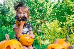 万圣节 孩子在与起重器o灯笼,把戏或款待的黑色在手中穿戴了 舔南瓜的上面的在w的小女孩 库存照片