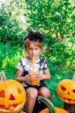 万圣节 孩子在黑饮用的南瓜鸡尾酒、把戏或款待穿戴了 在起重器o灯笼装饰附近的小女孩在向求爱 库存照片