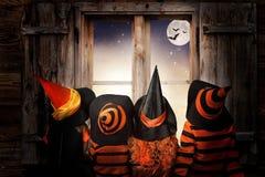 万圣节 巫婆和巫术师服装的孩子在晚上坐靠近窗口andand神色在天空和棒 库存照片