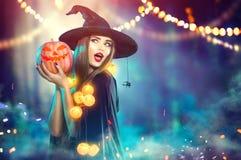 万圣节 巫婆用一个被雕刻的南瓜和魔术光 免版税库存图片