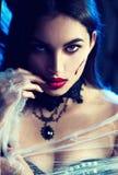 万圣节 巫婆用一个被雕刻的南瓜和魔术lightsHalloween 摆在黑暗中的秀丽性感的吸血鬼妇女 图库摄影