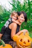 万圣节 拥抱母亲的女儿在起重器o灯笼附近在庭院里 党的装饰 愉快的系列 库存图片