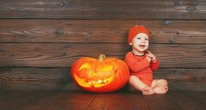 万圣节 有一台南瓜起重器的愉快的滑稽的婴孩在木 免版税库存照片