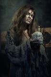万圣节 有一块头骨的邪恶的巫婆在他的手上 免版税库存照片
