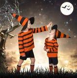 万圣节 服装的两个兄弟走在的可怕森林 男孩喂养他的兄弟蛇 库存照片
