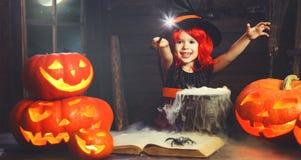 万圣节 烹调魔药用南瓜的小巫婆孩子和 免版税图库摄影