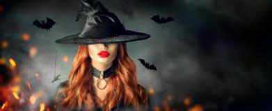 万圣节 纵向性感的巫婆 巫婆帽子的美丽的妇女有长的卷曲红色头发的 库存照片